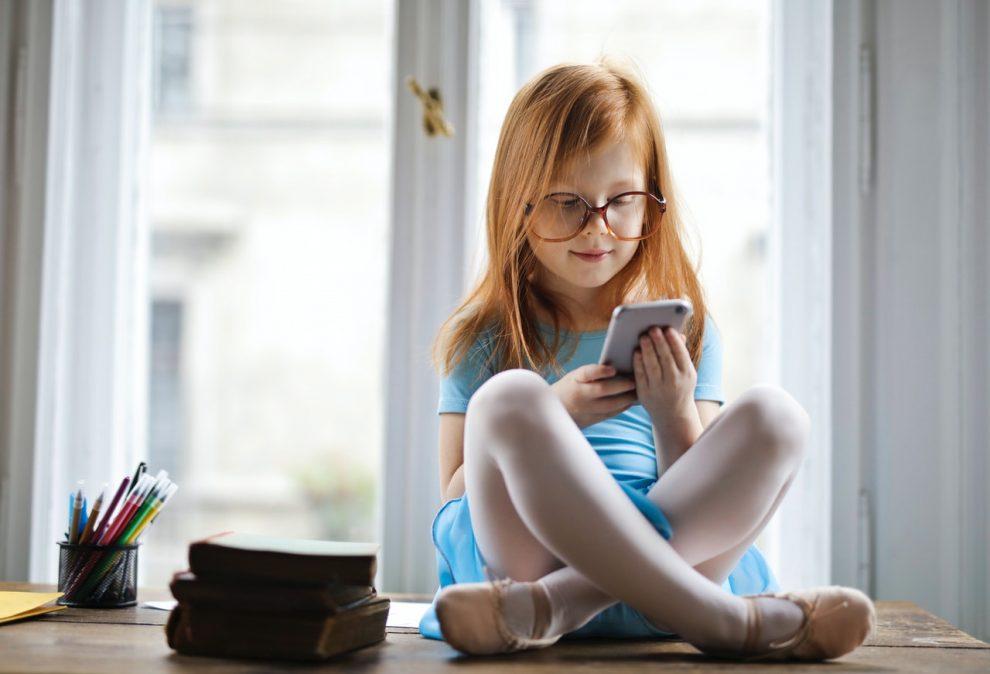 dziewczynka ze smartfonem, obok książki