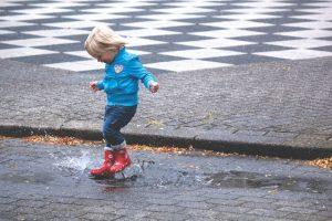 dziecko bawiące się w kałuży